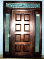Eight panel wood door with glass sidelites and transom