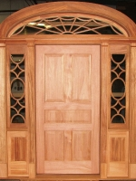 Spider web transom, sidelites with custom grills, six panel wood door